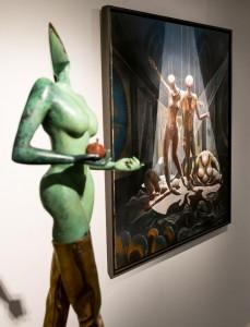 """Die Skulptur """"Lancet mit Apfel"""" versteht sich blendend mit dem """"Welttheater"""" dahinter, wenn man sie als Eva ansieht und den Werdegang der Menschheit hin zu bloßen Marionetten des Welttheaters begreift."""